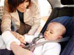 Woman buckling up baby